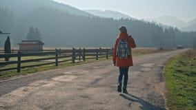 Flickan med ryggsäcken går på hus och berg för landsväg nära i nedgång stock video