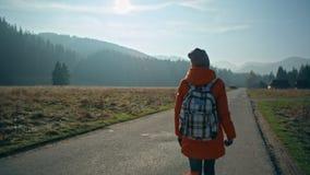 Flickan med ryggsäcken går på vägen som är fjällnära med härlig solilsken blick arkivfilmer