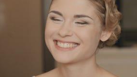 Flickan med smink ser henne i en spegel arkivfilmer