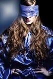 Flickan med snör åt maskeringen. Royaltyfri Foto