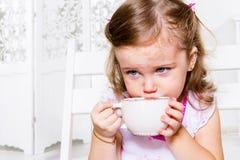 Flickan med teaen kuper royaltyfri foto