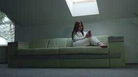 Flickan med telefonen som är hemmastadd på fönstret arkivfilmer