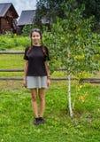 Flickan med trä krattar och ösregnar på landsvägen i by Copyspace Royaltyfri Fotografi