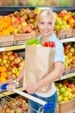 Flickan med vagnen räcker packen med nya grönsaker arkivfoton