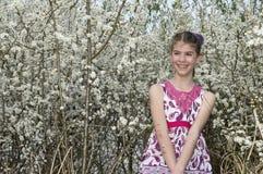 Flickan med vita blommor ser lycklig Royaltyfri Bild