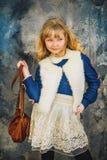 Flickan med vitt hår och en blått förbinder poserar Royaltyfri Fotografi