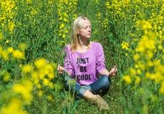 Flickan mediterar i ett gräs Arkivbilder