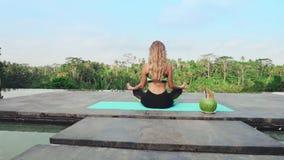Flickan mediterar i ett tropiskt land