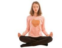 Flickan mediterar, medan sitta i lotusblommapositionen arkivbilder