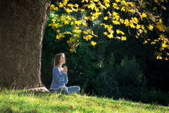 Flickan mediterar sammanträde på gräset under lönnträd i höst Arkivbild