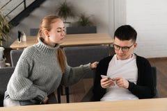 Flickan misstänker hennes man, i att fuska på henne och att spionera att sitta nära i kafét Misstrobegrepp royaltyfria bilder