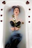 Flickan mjölkar vatten - stearinljus för röda rosor för bad Royaltyfri Bild