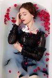 Flickan mjölkar vatten - stearinljus för röda rosor för bad Royaltyfria Foton