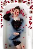 Flickan mjölkar vatten - stearinljus för röda rosor för bad Arkivfoton