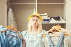 Flickan nära en garderob med kläder kan inte välja vad för att bära Det tunga primaa begreppet har ingenting att bära arkivbilder