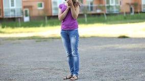 Flickan något trycker på på telefonen lager videofilmer