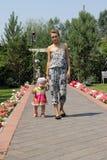 Flickan och barnet som går på aveny Royaltyfria Bilder