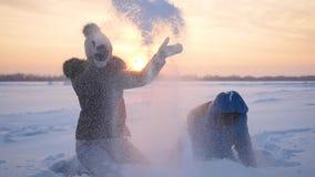 Flickan och barnet som kastar snö över honom och, tycker om den i vinter parkerar på solnedgången stock video