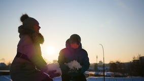 Flickan och barnet som kastar snö över honom och, tycker om den i vinter parkerar på solnedgången arkivfilmer