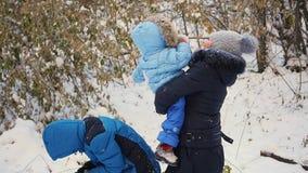 Flickan och barnet som kastar snö över honom och, tycker om den i vintern parkerar arkivfilmer