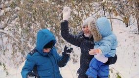 Flickan och barnet som kastar snö över honom och, tycker om den i vintern parkerar stock video