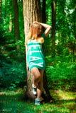 Flickan och det stora trädet i skogen Royaltyfria Bilder