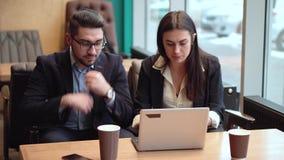 Flickan och en grabb i affärsdräkter sitter ner på en tabell med en bärbar dator och ett kaffe för att diskutera detaljerna av ar stock video