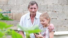 Flickan och ett åldringpensionärsammanträde utomhus i trädgården av trädgården i en omfamning Utveckling stock video