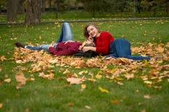 Flickan och grabben i röda tröjor och jeans sitter i parkerar på det gröna gräset i de gula lönnlöven, flickaleendena A arkivbilder