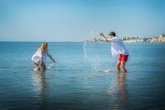 Flickan och grabben sprutade in i havet Royaltyfria Foton