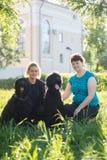 Flickan och hennes svarta för ryss två Terrier för moder och sammanträde på gräset i parkera fotografering för bildbyråer