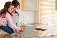 Flickan och hon fostrar genom att använda en bärbar dator Arkivbild