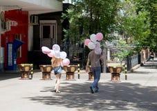 Flickan och mannen bär bollar Royaltyfri Bild