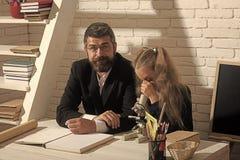 Flickan och mannen sitter på skrivbordet och ser in i mikroskopet arkivbilder