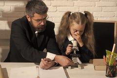 Flickan och mannen sitter vid skrivbordet och ser in i mikroskopet arkivfoton