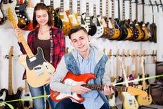 Flickan och pojken 15-20 gamla år avgör på passande ampere Royaltyfri Bild