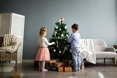 Flickan och pojken klär upp julgranen glada lyckliga ferier för jul Fotografering för Bildbyråer