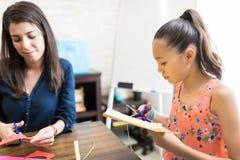 Flickan och privata handleder Cutting Craft Papers på tabellen arkivfoto