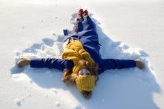Flickan och snö, ung flicka i lilor täcker, och en grå hatt och gulinghalsduk ligger på snön, flicka gör en snöängel royaltyfri bild