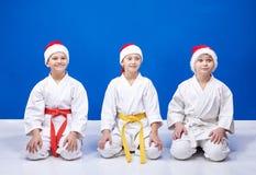 Flickan och två pojkar som sitter i en karate, poserar Royaltyfri Foto