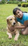 Flickan omfamnar lovingly hans älsklings- hund Arkivfoton