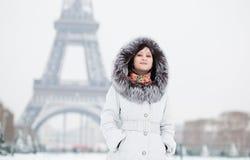 Flickan pälsfodrar in huven med Eiffelen står hög i bakgrund Royaltyfri Bild