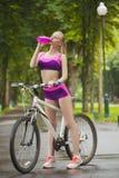 Flickan på cykeln som stoppas, och dricksvatten från flaskan Royaltyfria Foton