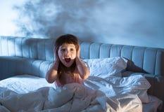 Flickan på den skrikiga beläggningen för säng hans öron med hans händer royaltyfri bild