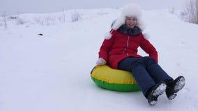 Flickan på den snöig plattan rullar ner från det höga snöig berget och skratt med nöje Tonåringen spelar i vinter med slädar stock video