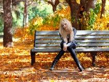 Flickan på en bänk parkerar in royaltyfri foto