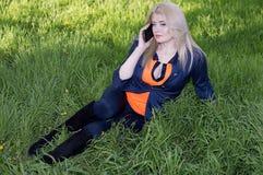 Flickan på en gräsmatta med telefonen, ett gräs Arkivbild