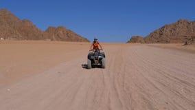 Flickan på en kvadratcykel rider till och med öknen av Egypten på bakgrund av berg l?ngsam r?relse stock video