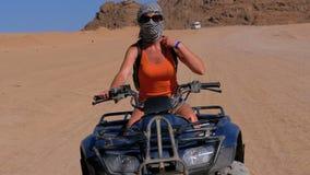 Flickan på en kvadratcykel rider till och med öknen av Egypten på bakgrund av berg l?ngsam r?relse lager videofilmer