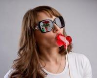 Flickan på ett datum kysser godisen i formen av en hjärta, symbol av l Arkivfoto